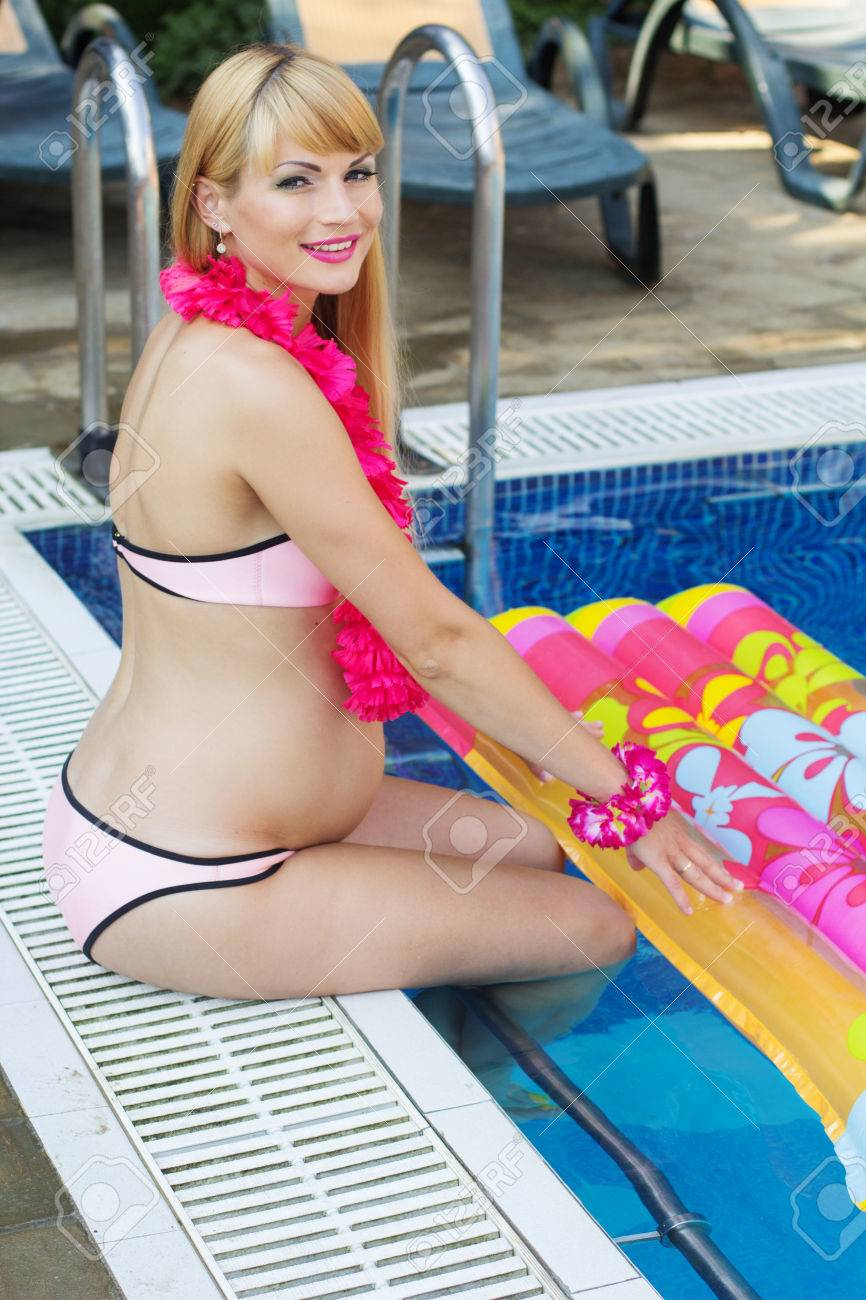0f349821e78dc Beautiful pregnant blonde woman is sitting with colorful mattress near blue  water of swimming pool Stock