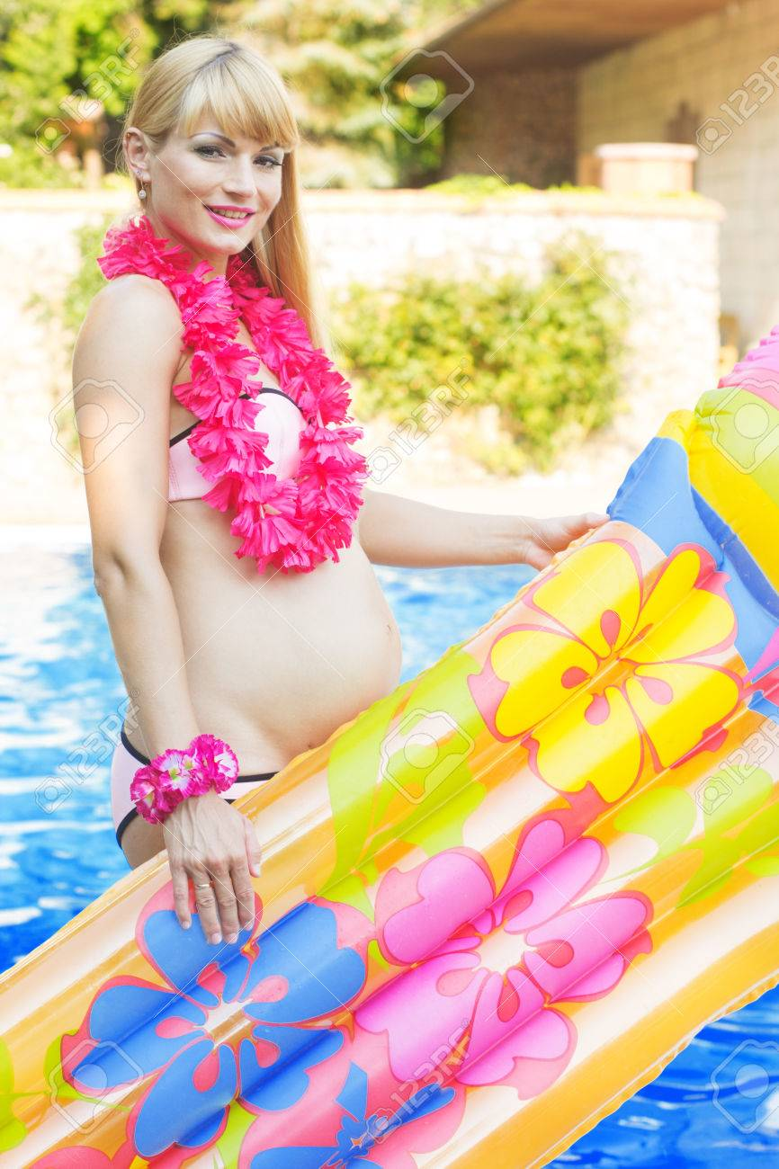 64491646220c2 Beautiful pregnant blonde girl is sitting with colorful mattress and  hawaiian flowers near blue water of