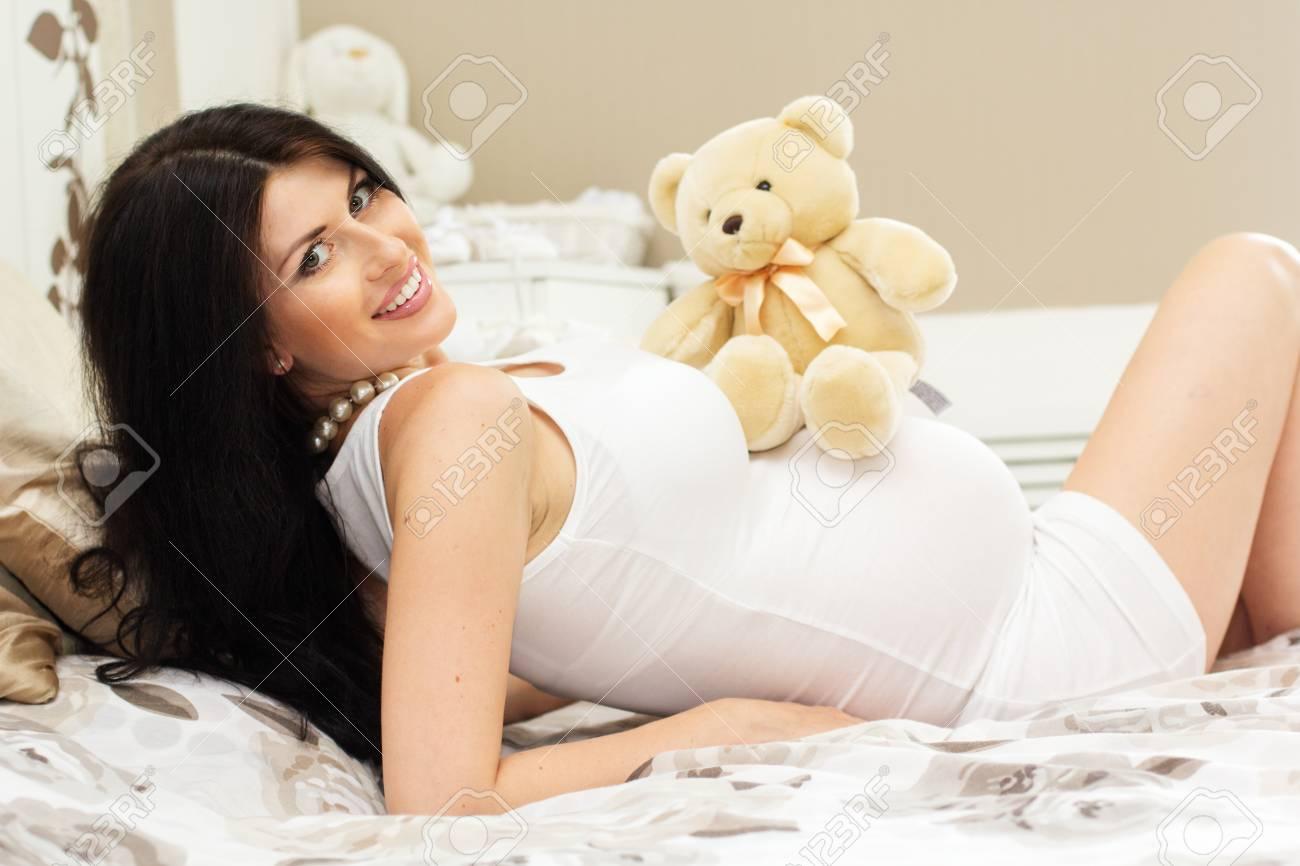 Bella Donna Incinta è Sdraiato Sul Letto E Abbracciare Giocattolo ...