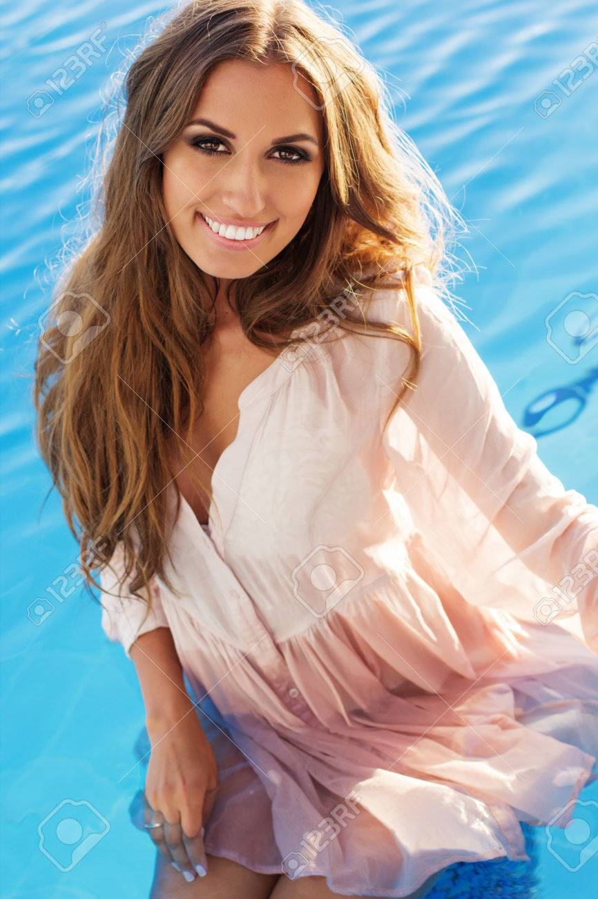 sexy smiling woman with tanned skin is wearing wet shirt swimming