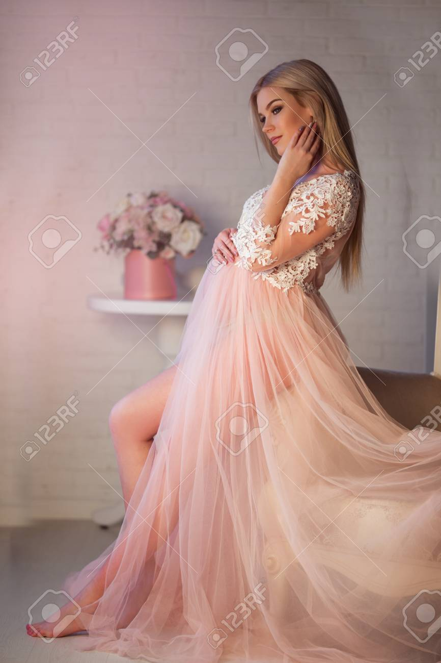 004b062ef Pretty blonde pregnant young girl is wearing luxury pink lingerie dress at  home in cozy interior