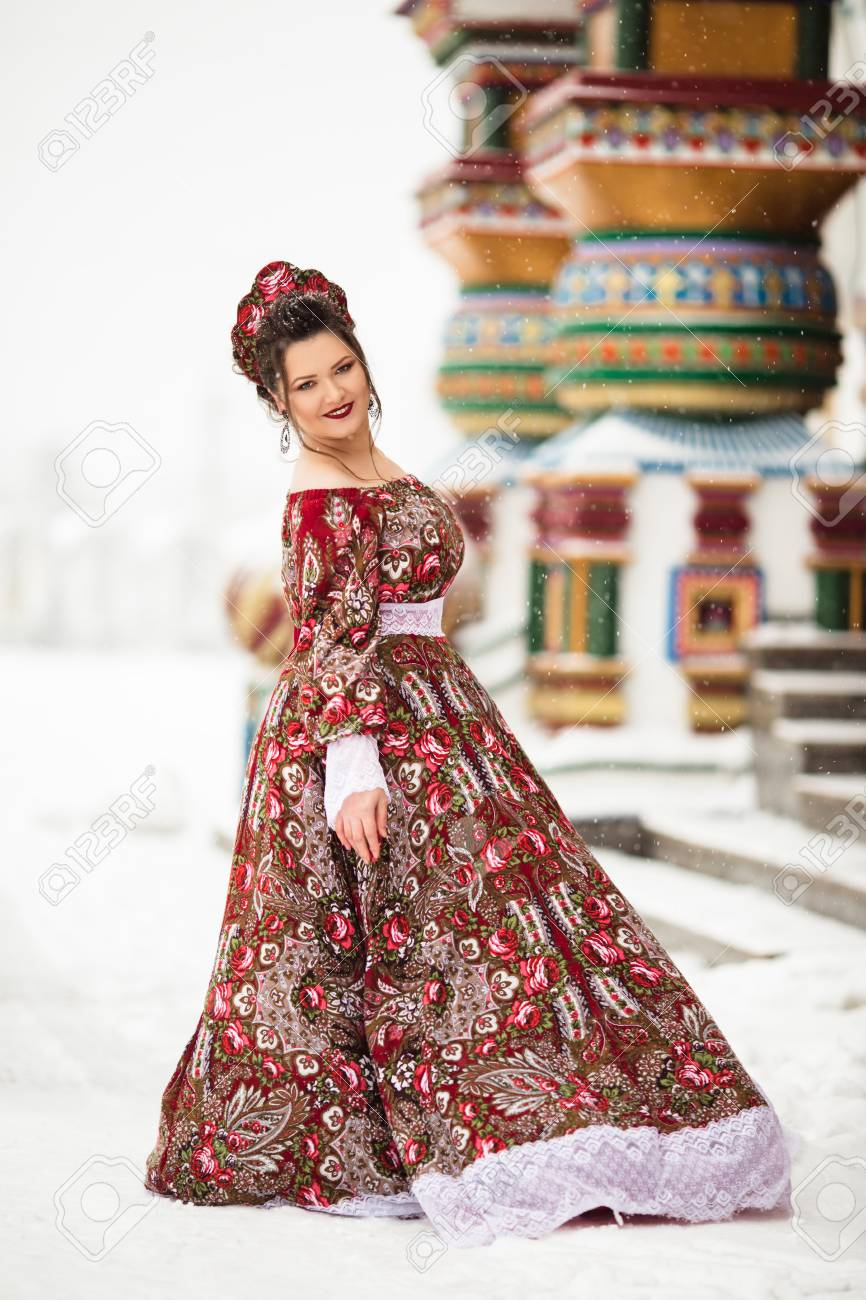 2aea2e11a644a Beautiful happy woman is wearing traditional russian clothes in winter park  Stock Photo - 114170625