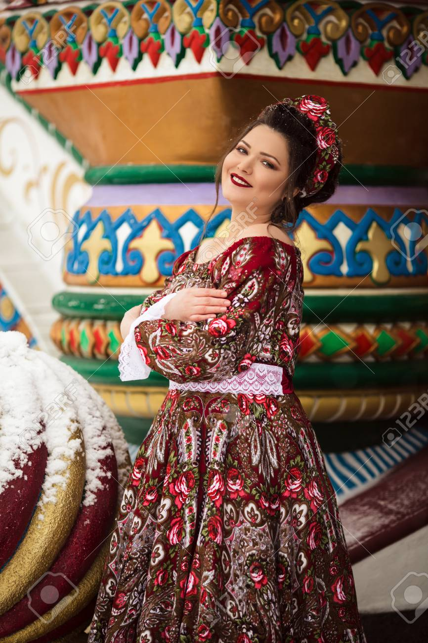 c9aa6dab9665e Beautiful happy woman is wearing traditional russian clothes in winter park  Stock Photo - 114170627