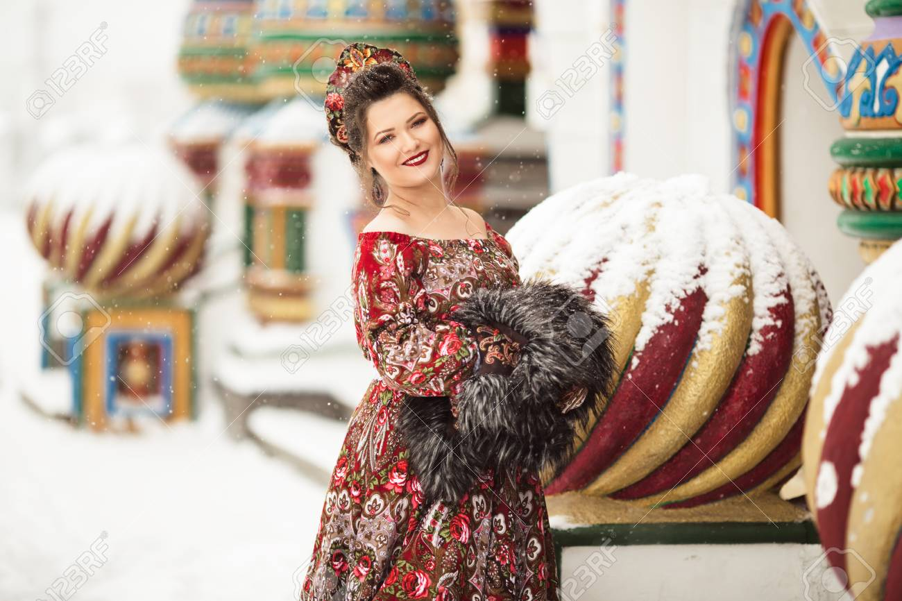 193e2dca35986 Beautiful happy woman is wearing traditional russian clothes in winter park  Stock Photo - 114170628