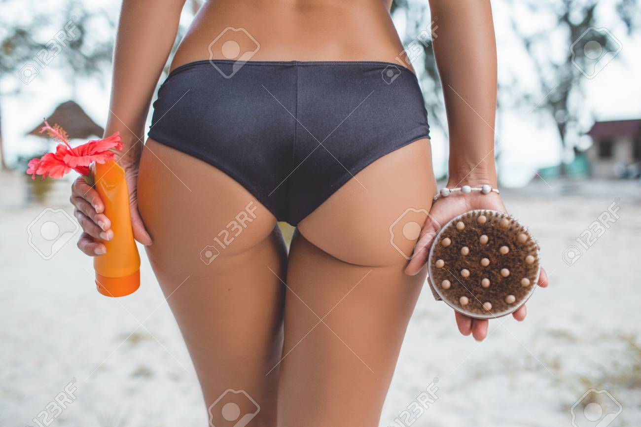 Young woman on the beach is holding brush and cream in hands antu cellulite treatment. Cellulite problem concept. - 124869633