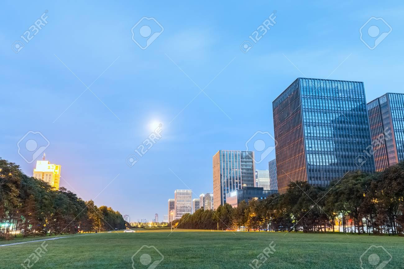 modern buildings with green space in nightfall binhai new district