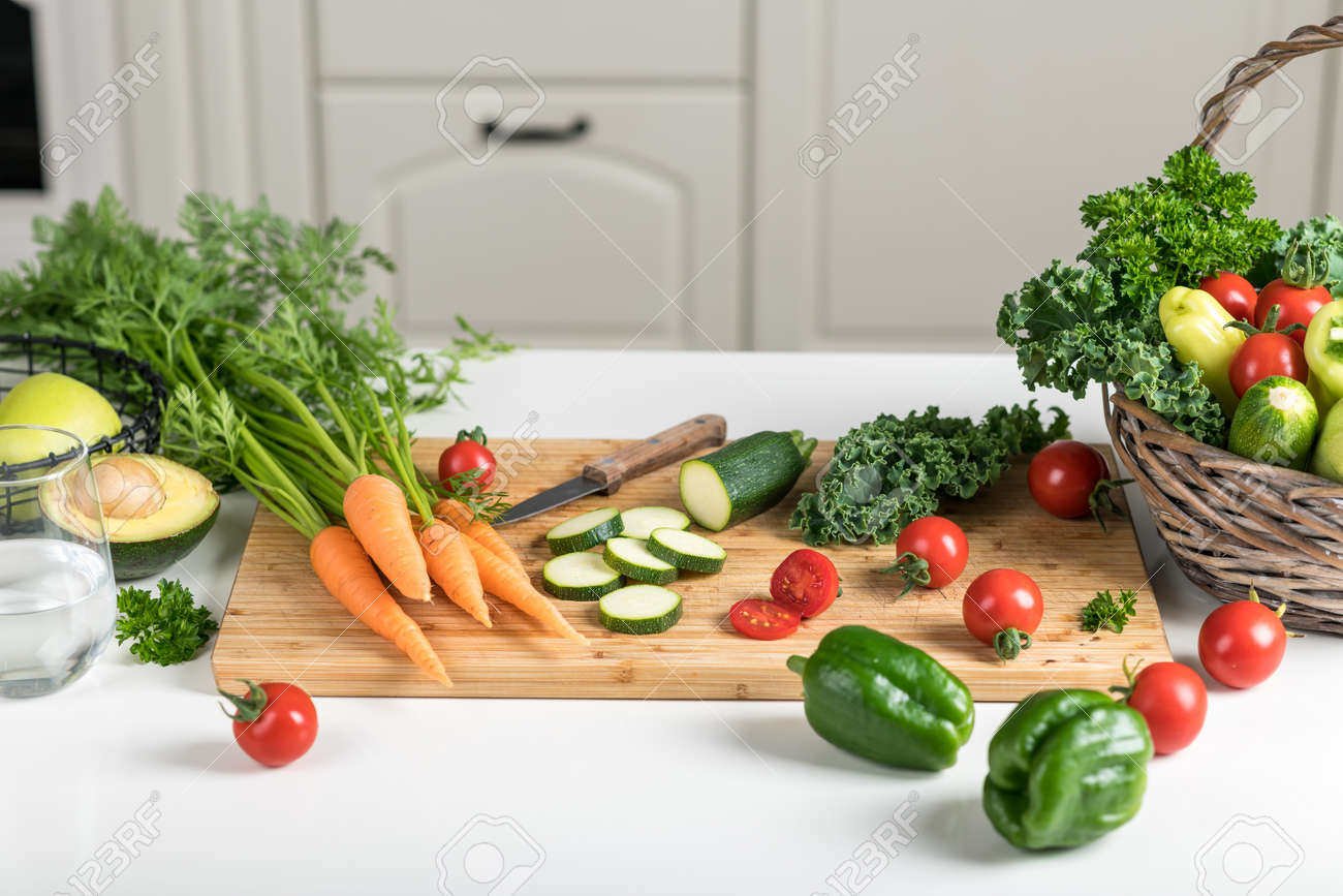 Healthy food concept. Fresh vegetables on a white table on a cutting board in the kitchen. Selective focus - 155907265