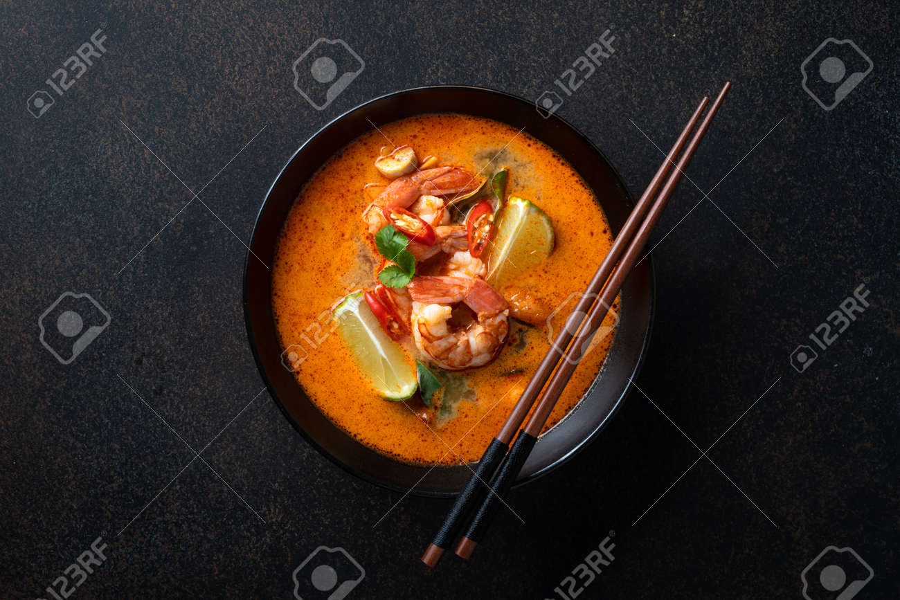 Tom Yum soup with shrimp in a ceramic black bowl with chopsticks on a dark background, top view - 169788399