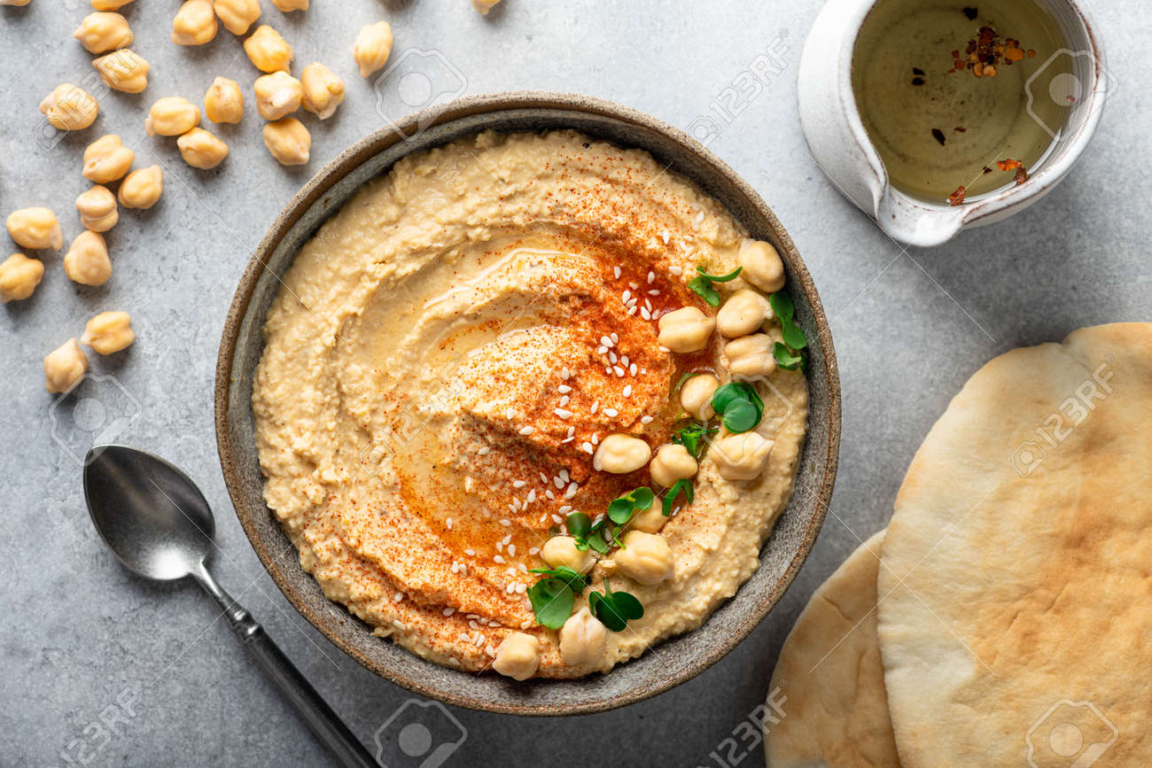 hummus in a ceramic bowl on a light background, top view - 169788397