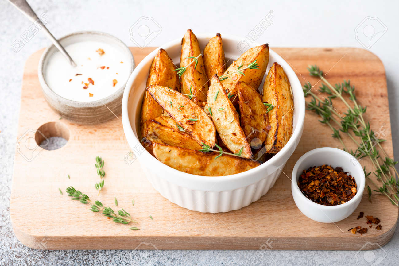 baked potato wedges with sauce on a light background - 169788402