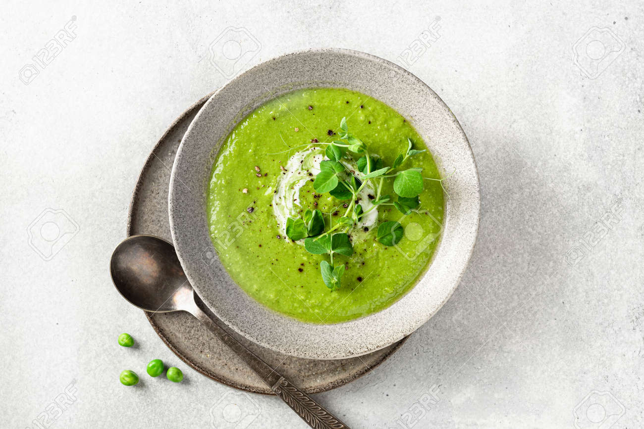Green pea soup in a ceramic bowl on gray concrete background, top view - 169788417