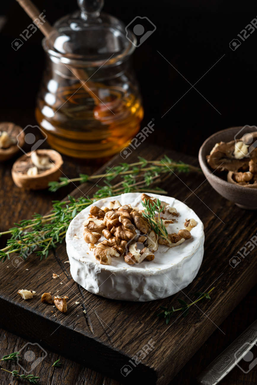 brie cheese with walnuts and honey on a wooden cutting board . Selective focus, dark background - 169788468