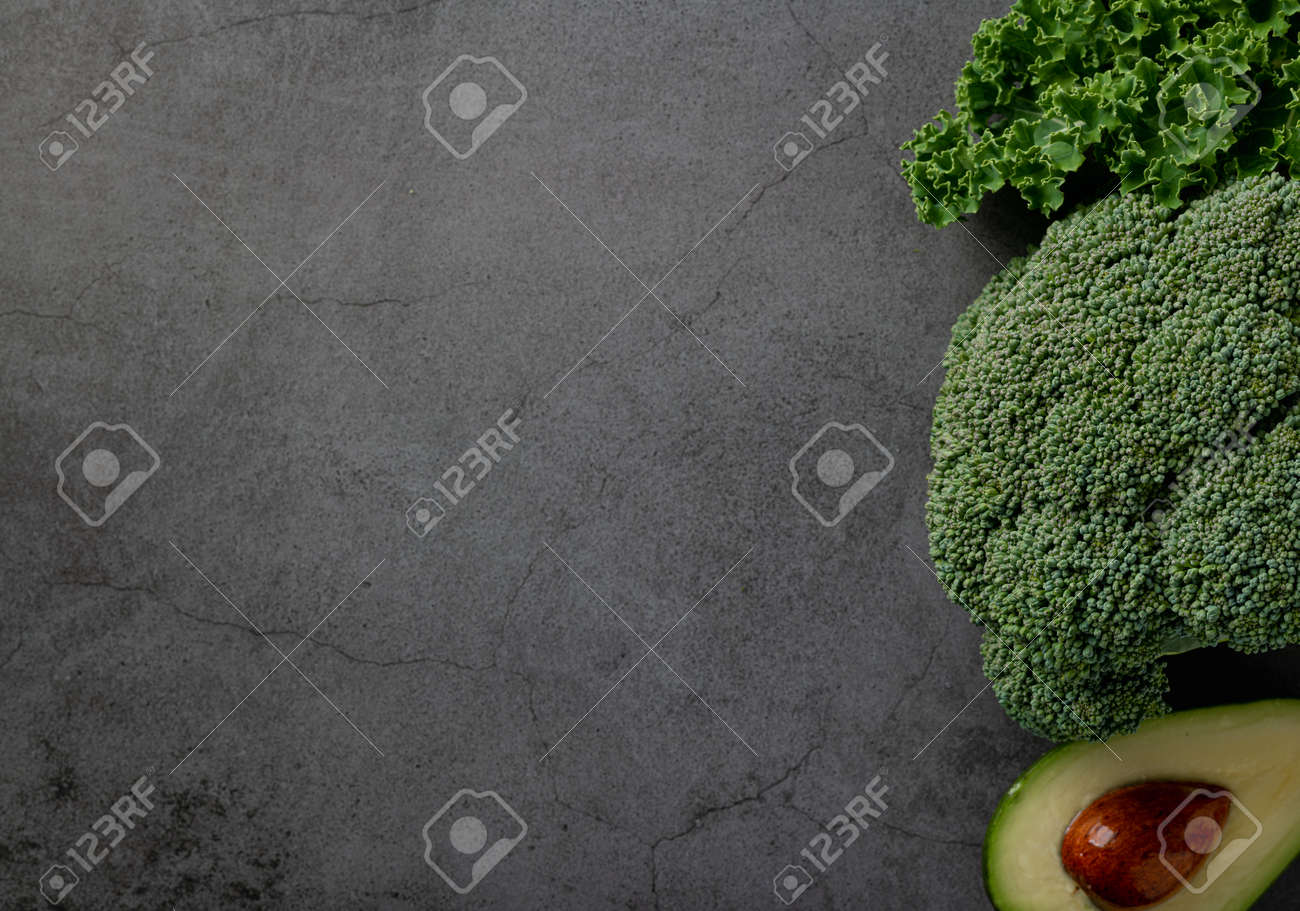 Avocado, kale and broccoli, detox dieting concept. Green vegetables on a dark stone background, top view - 169788500