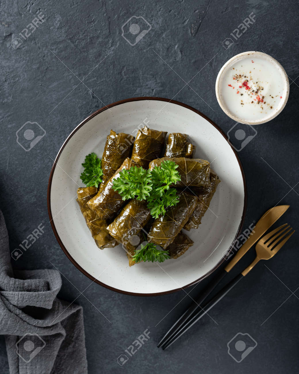 Dolma - stuffed grape leaves with rice and meat on a dark background, view from above. Traditional Greek. Caucasian and Turkish cuisine - 169788501