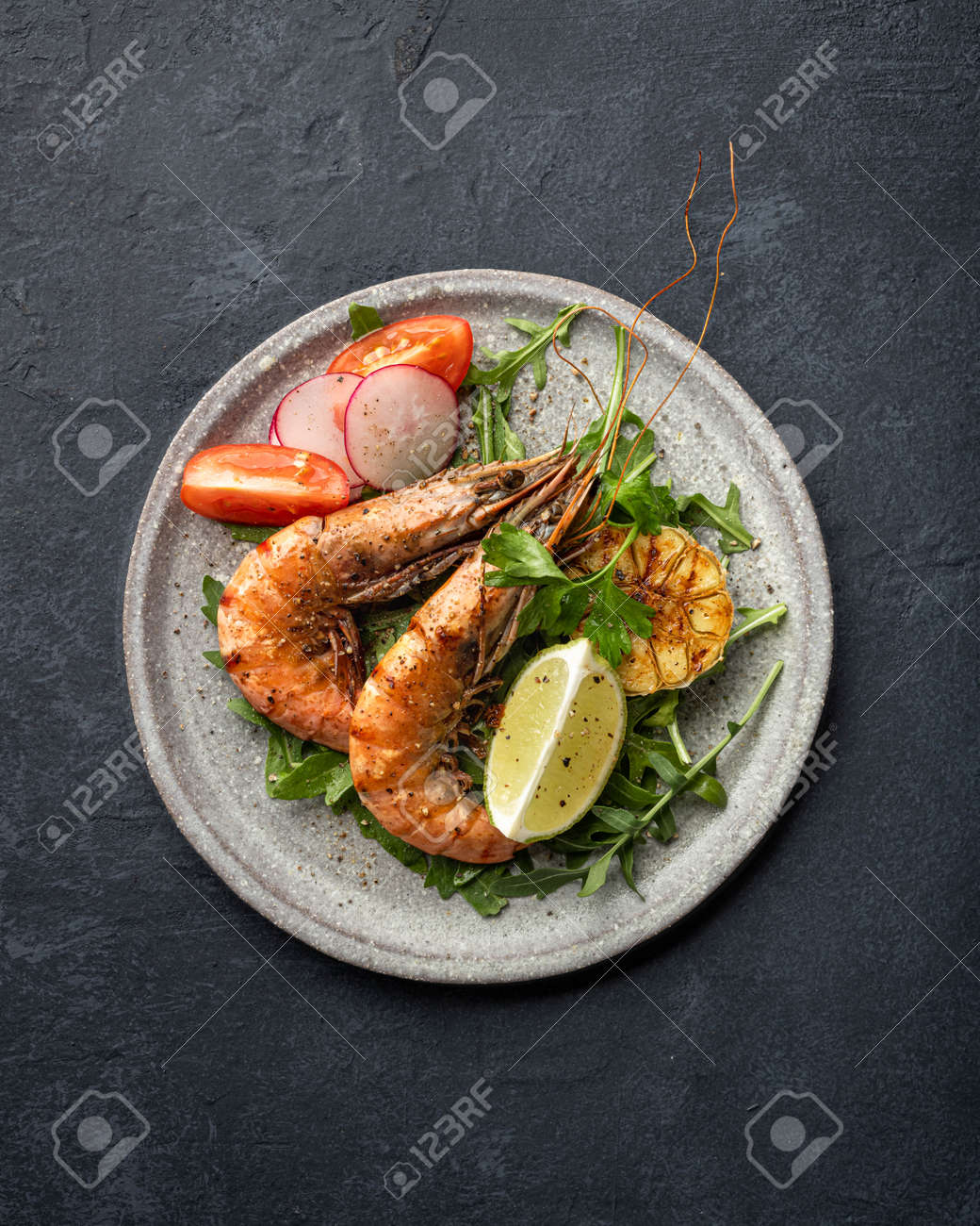 grilled tiger prawns with vegetables on a ceramic plate, top view - 169788531