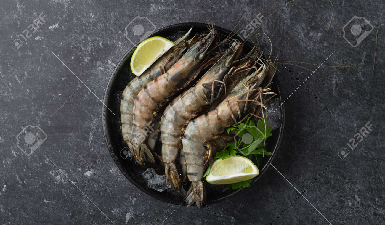 raw black tiger prawns on ice on a black background, top view, selective focus - 169788533