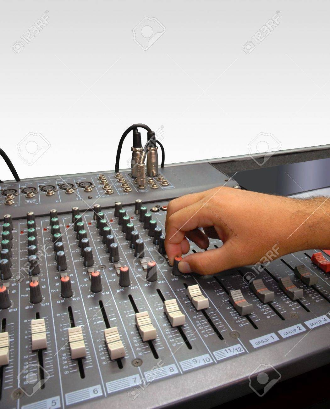 Sound Mixer Console of a Record Studio. Hand of a man making adjustments with a control knob. White background - 5652429