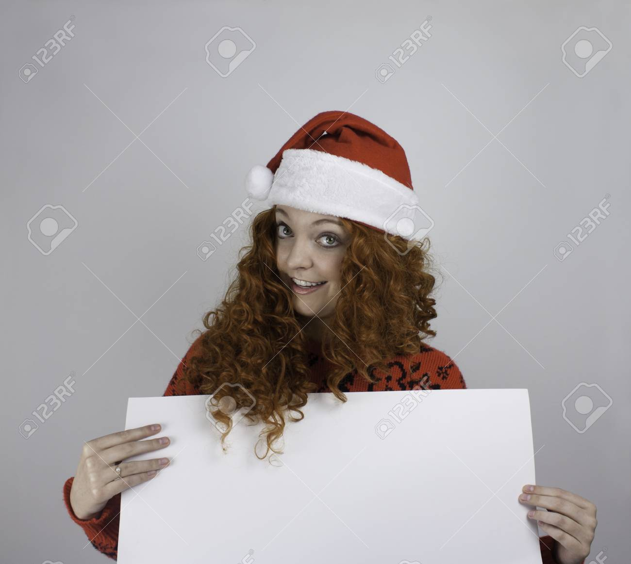 36898c7930326 Pretty young woman wearing Santa hat and holding blank sign Stock Photo -  25783572