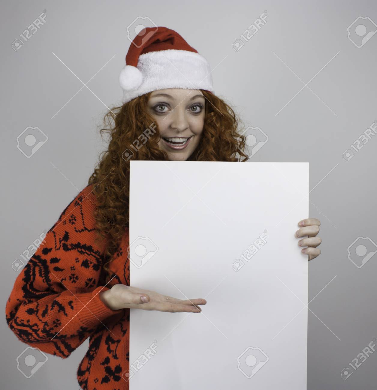 2cc304d5ac7a6 Pretty young woman wearing Santa hat and holding blank sign Stock Photo -  25783577