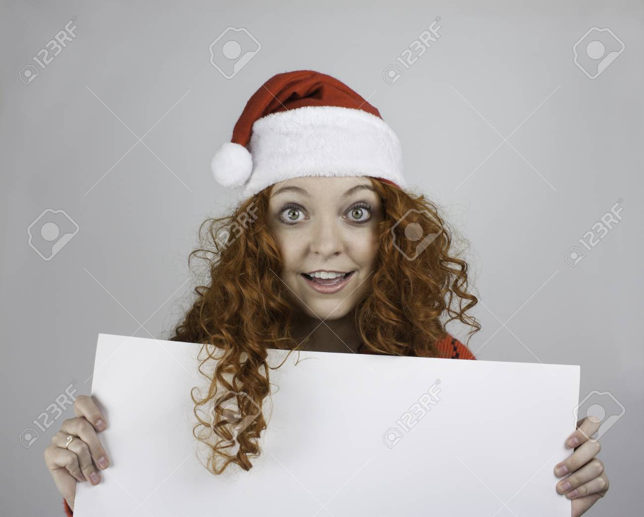 f0703e0d7546a Pretty young woman wearing Santa hat and holding blank sign Stock Photo -  25783566