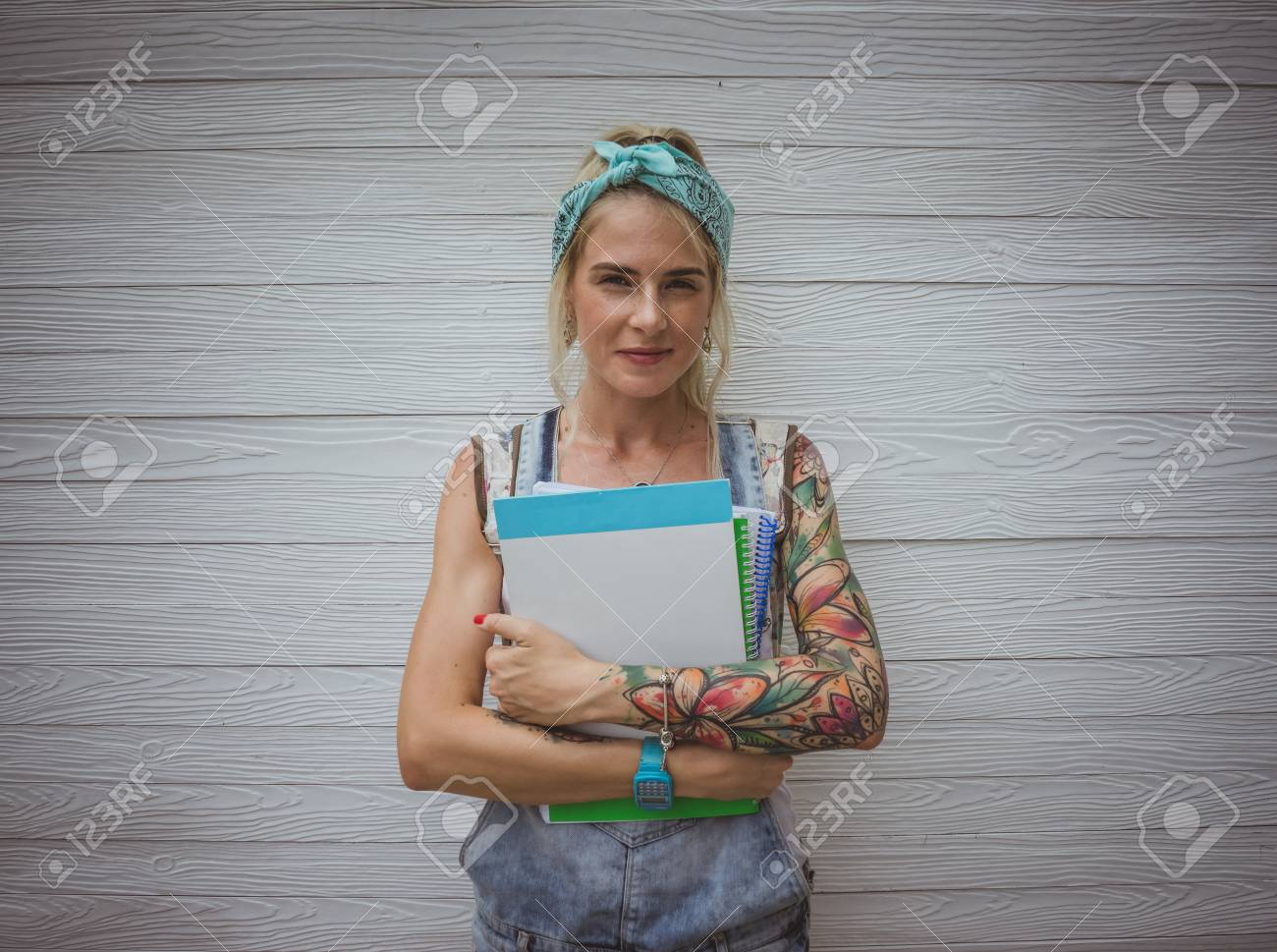 female student is standing by the white wall with notebooks in his hands in anticipation of classes. Modern girl. Model of tattoos - 94299822