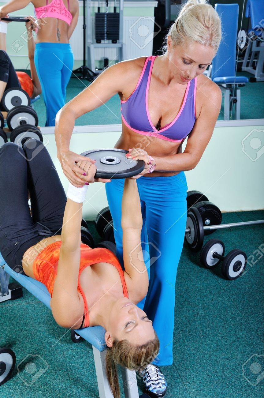 Two beautiful women exercising in gym with weights Stock Photo - 15265194
