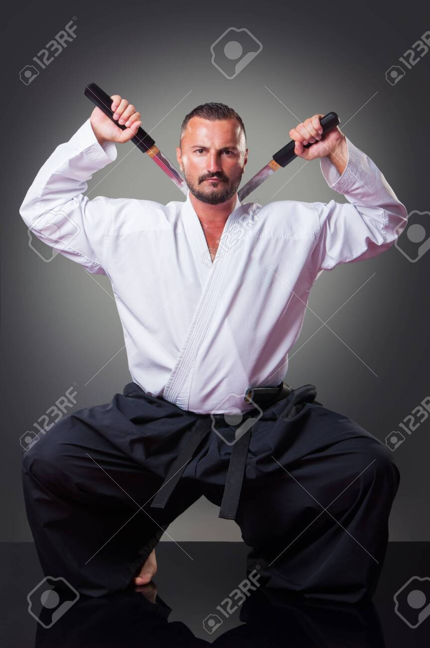 Handsome male karate player posing with the sword on the gray
