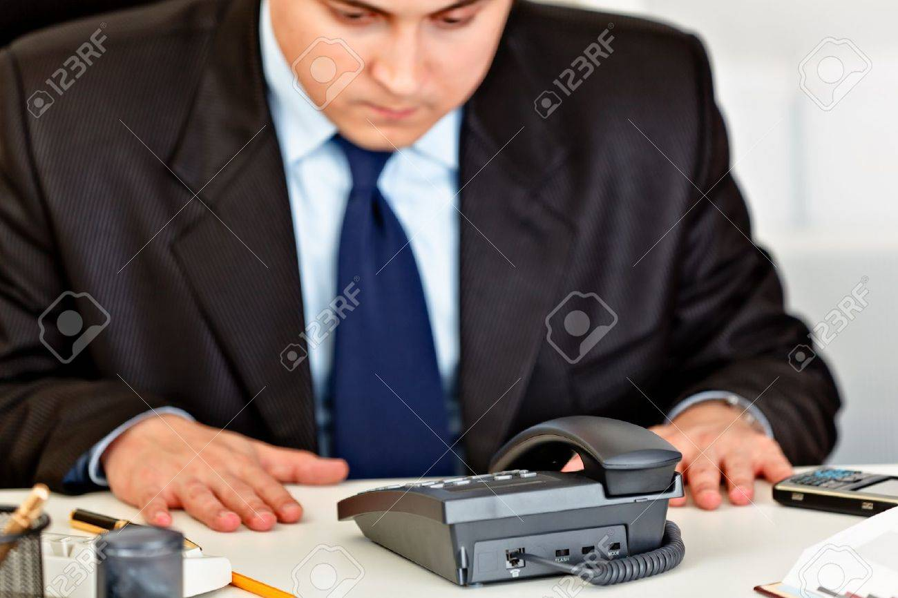 Concentrated business man sitting at office desk and expecting phone call Stock Photo - 8846275