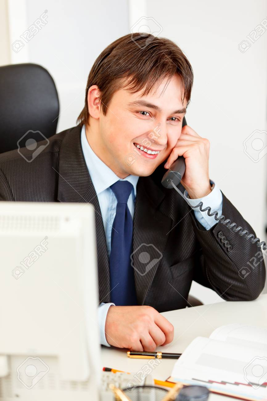 Smiling businessman sitting at office desk and talking on the phone Stock Photo - 8847972