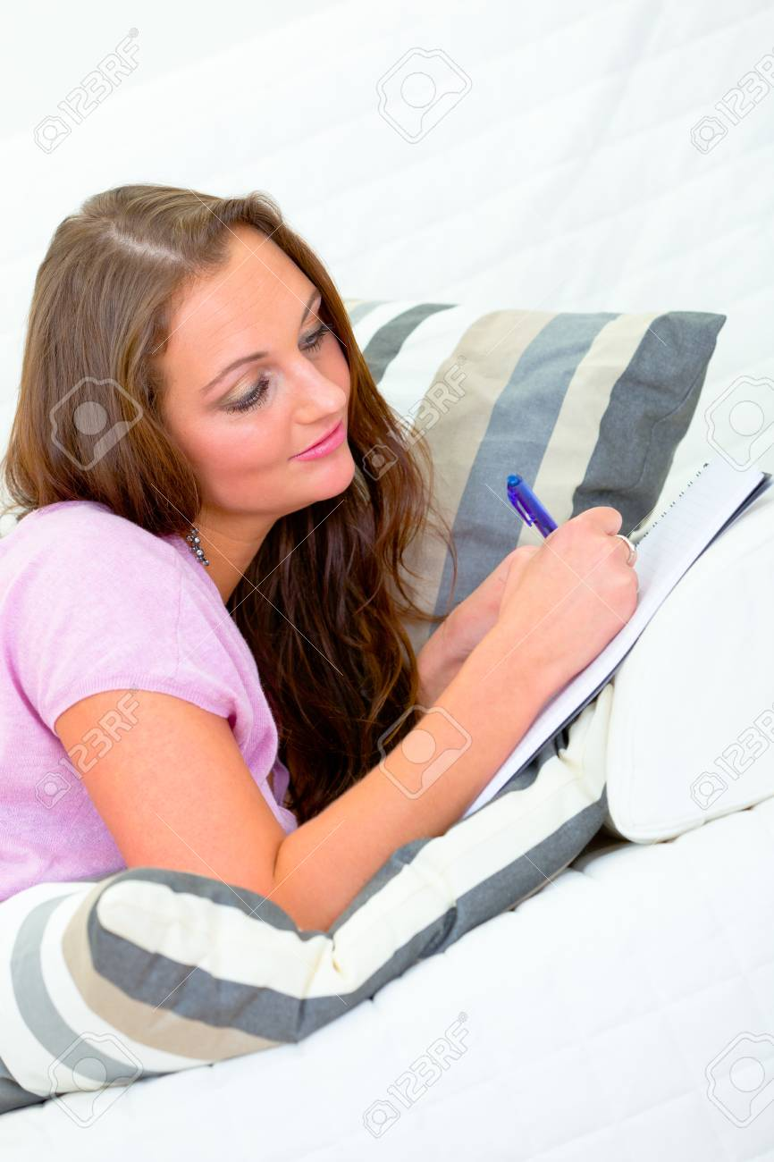 Pensive pretty woman lying on sofa at home and writing in notebook Stock Photo - 8955443