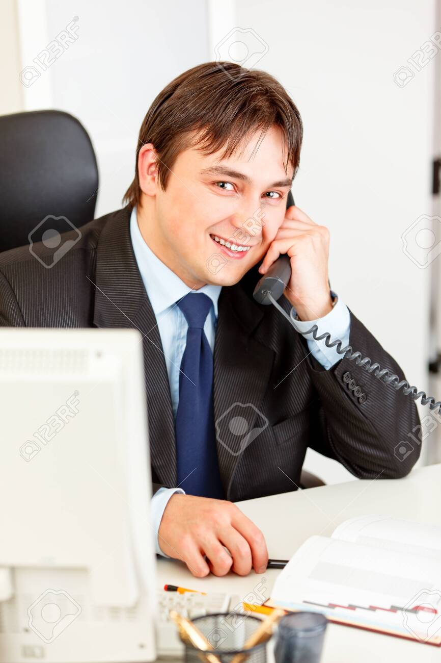 Friendly businessman sitting at office desk and talking on phone Stock Photo - 9024878