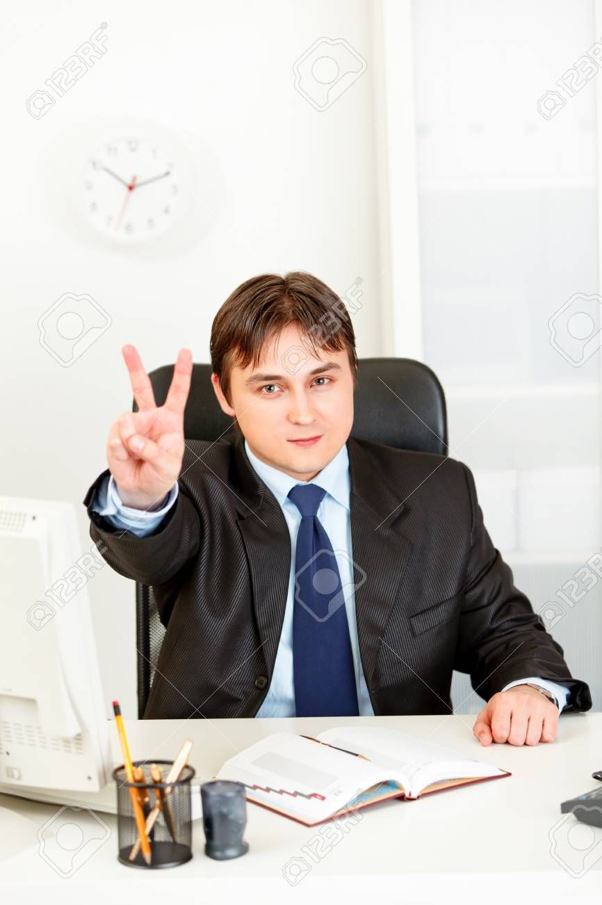 Confident modern business man sitting at office desk and showing victory gesture Stock Photo - 9403967