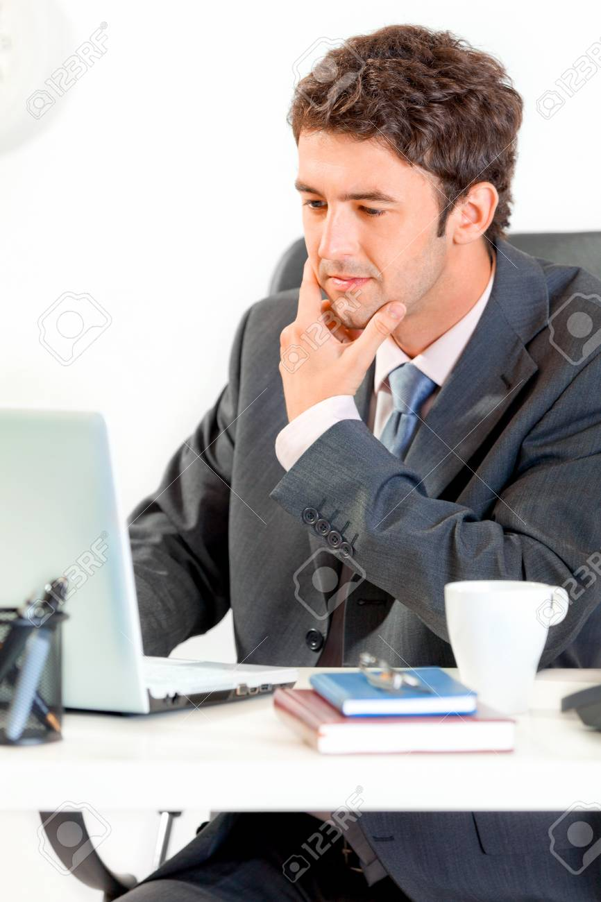 Thoughtful modern businessman sitting at office desk and working on laptop Stock Photo - 9620731