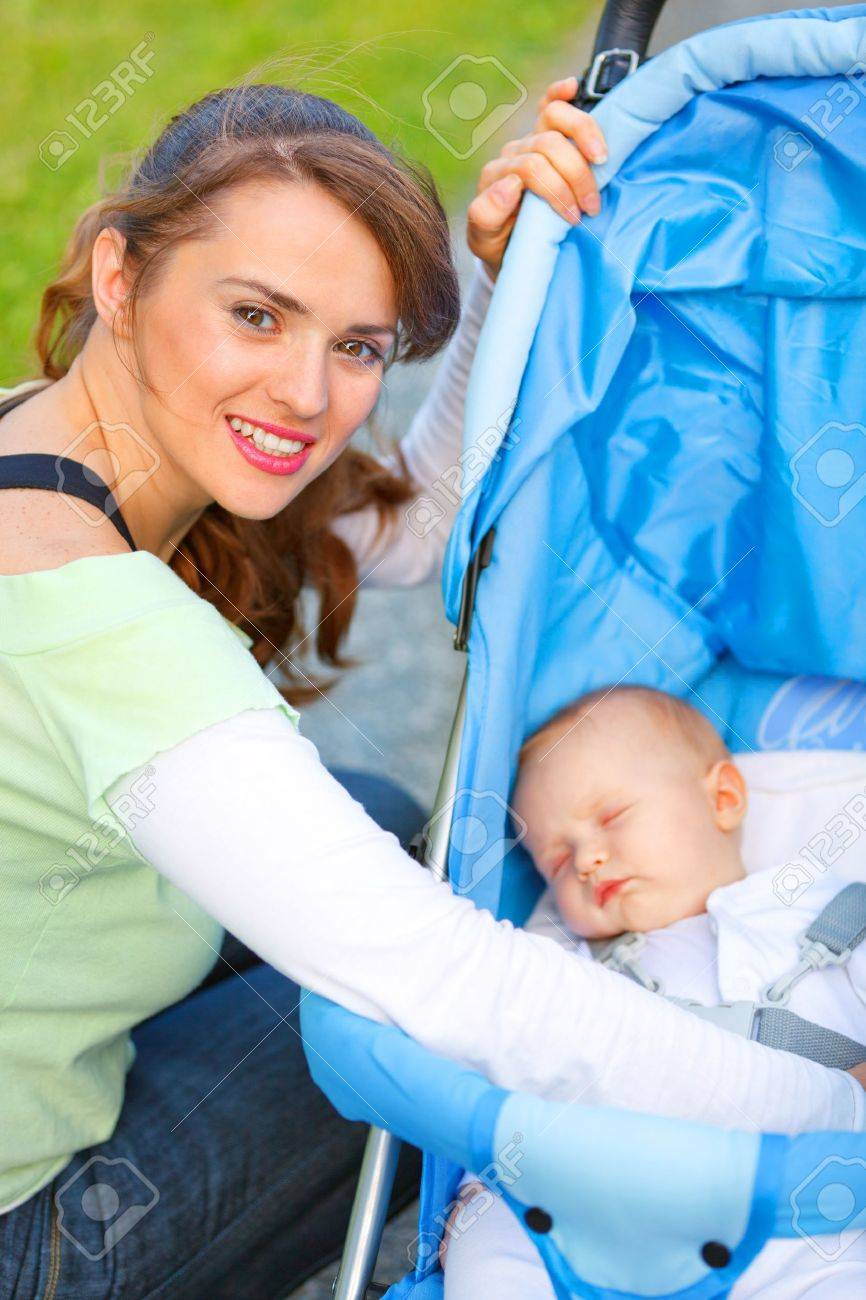 Smiling young mother sitting near stroller and taking care about her baby Stock Photo - 11640439