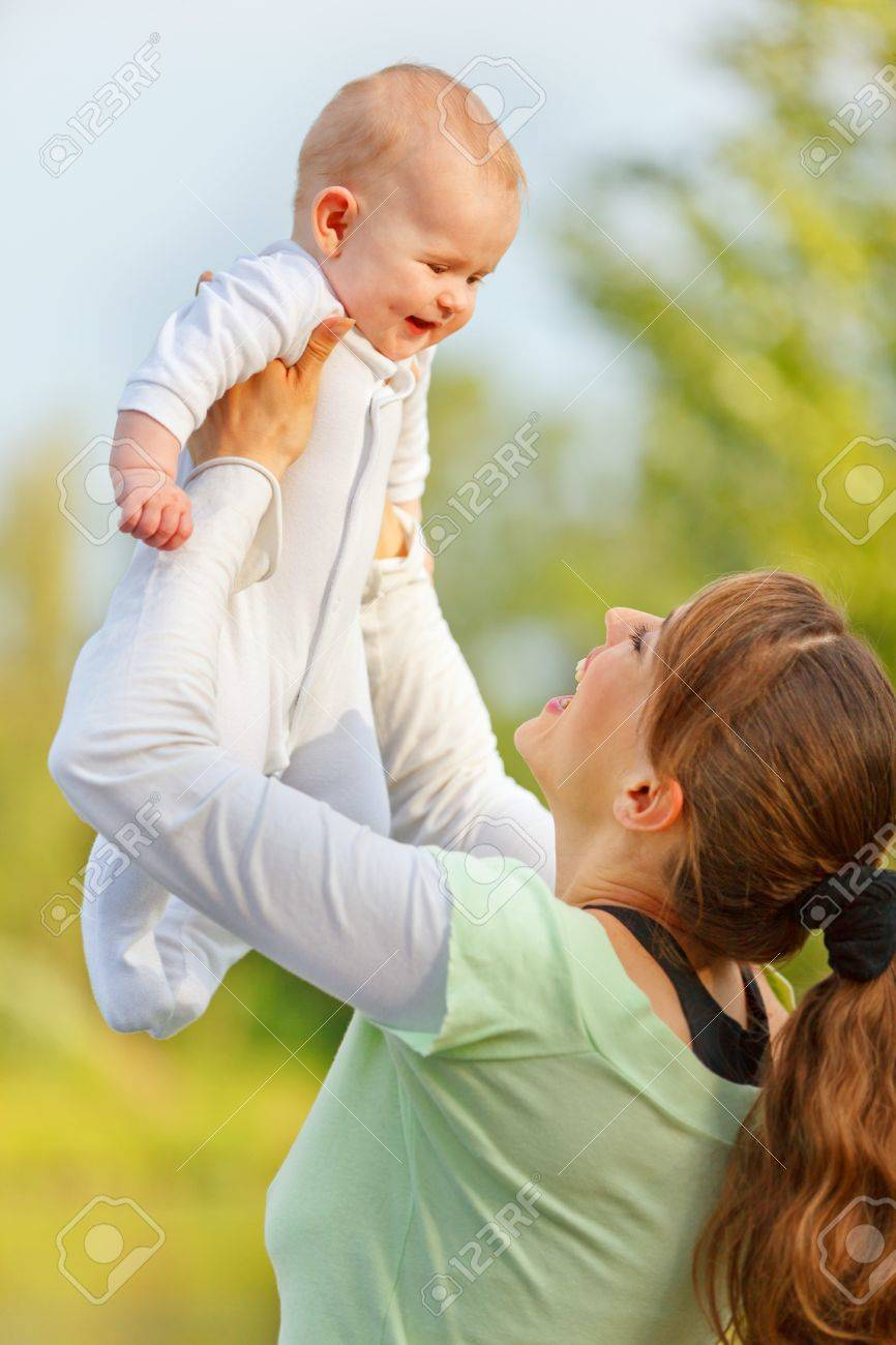 Happy young mother playing with smiling baby girl in park Stock Photo - 11640433
