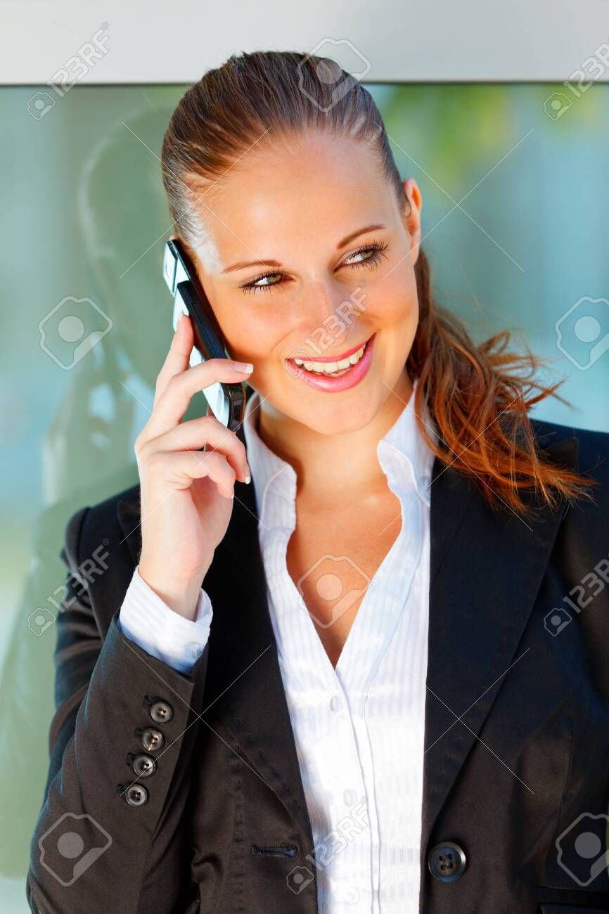 Portrait of modern smiling business woman talking on mobile at office building Stock Photo - 9792749
