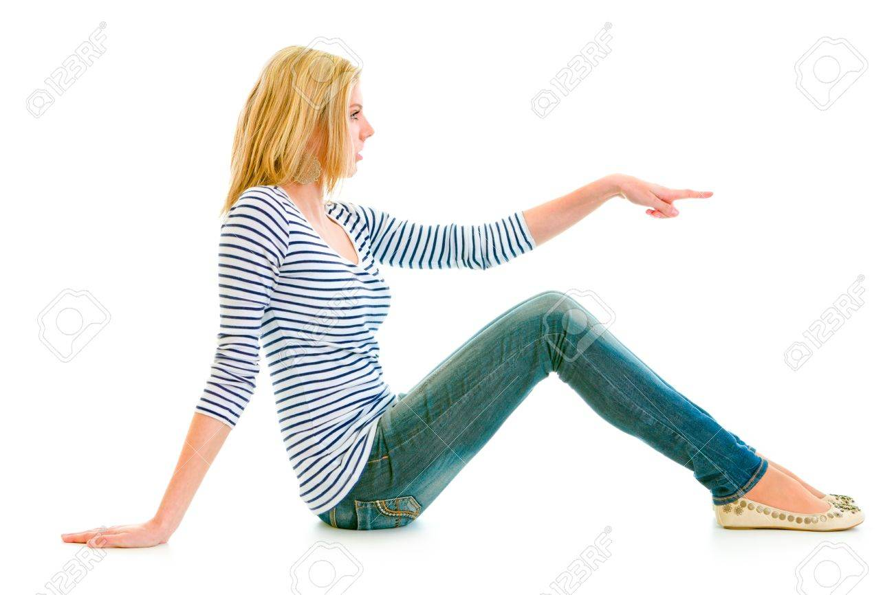 Beautiful teen girl sitting on floor and pointing finger at copy-space isolated on white Stock Photo - 9792797