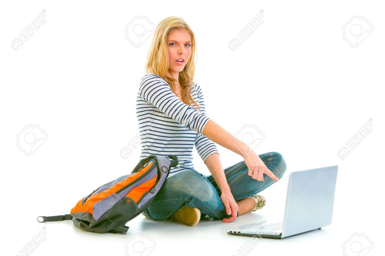 Surprised teenager sitting on floor with backpack and pointing in laptop isolated on white Stock Photo - 10344765