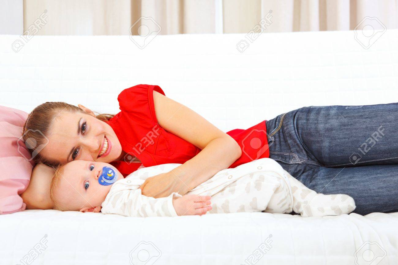 Smiling mother and baby laying on couch Stock Photo - 10844009