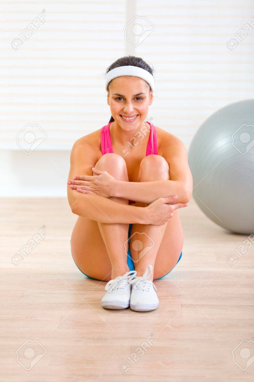 Smiling fit girl in sportswear sitting on floor at living room Stock Photo - 11001761