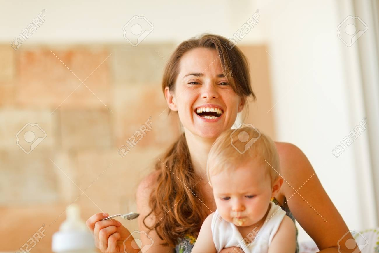 Portrait of laughing young mother feeding baby Stock Photo - 11419651
