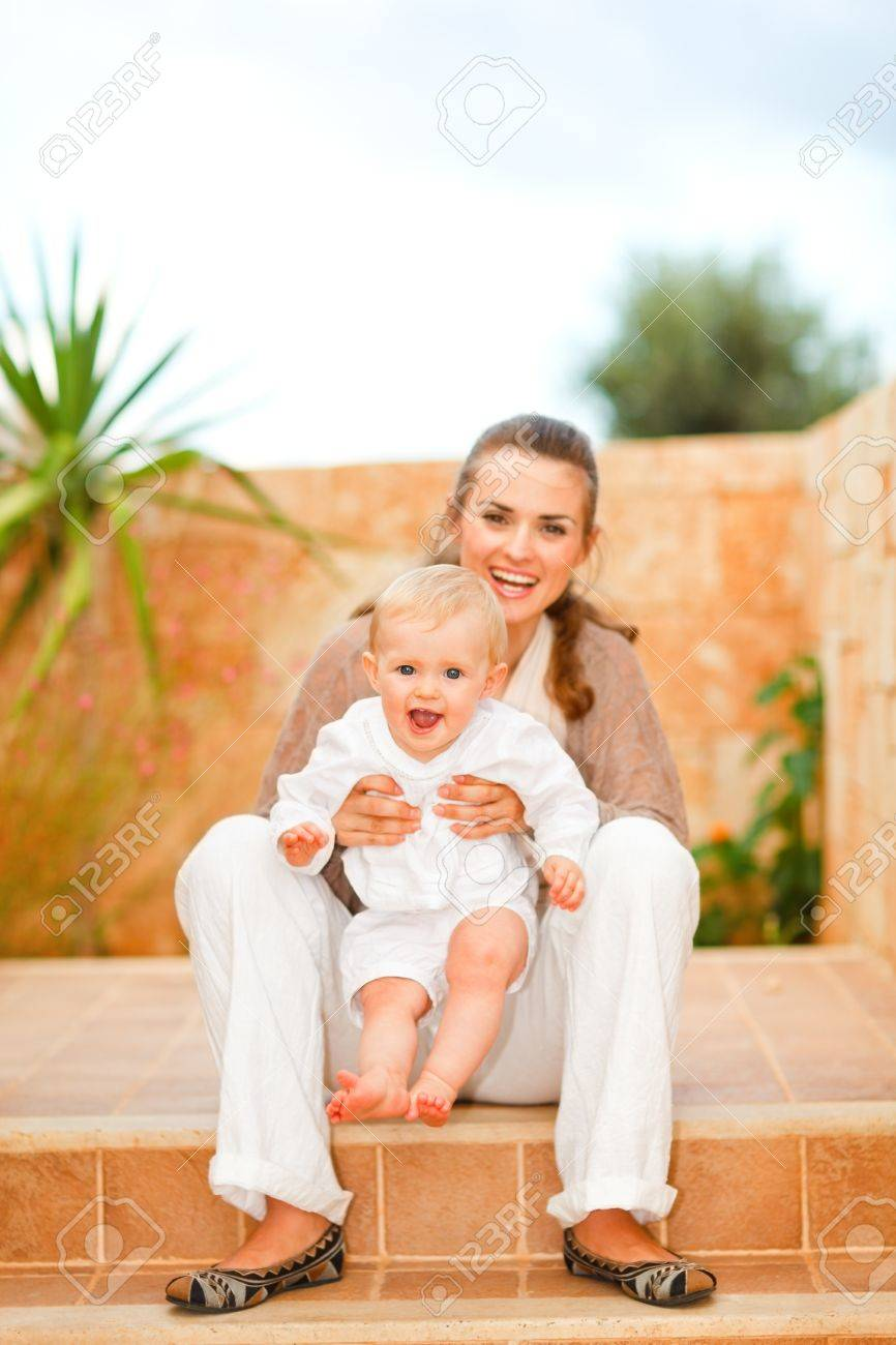Portrait of smiling mother and happy baby sitting on staircase Stock Photo - 11419649