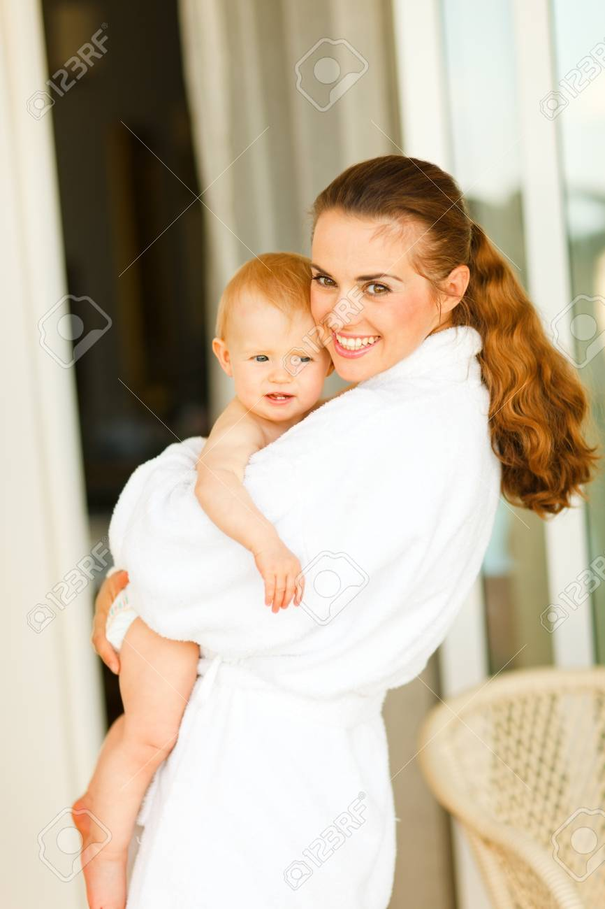 Portrait of young mother in bathrobe with baby in hand Stock Photo - 11419626