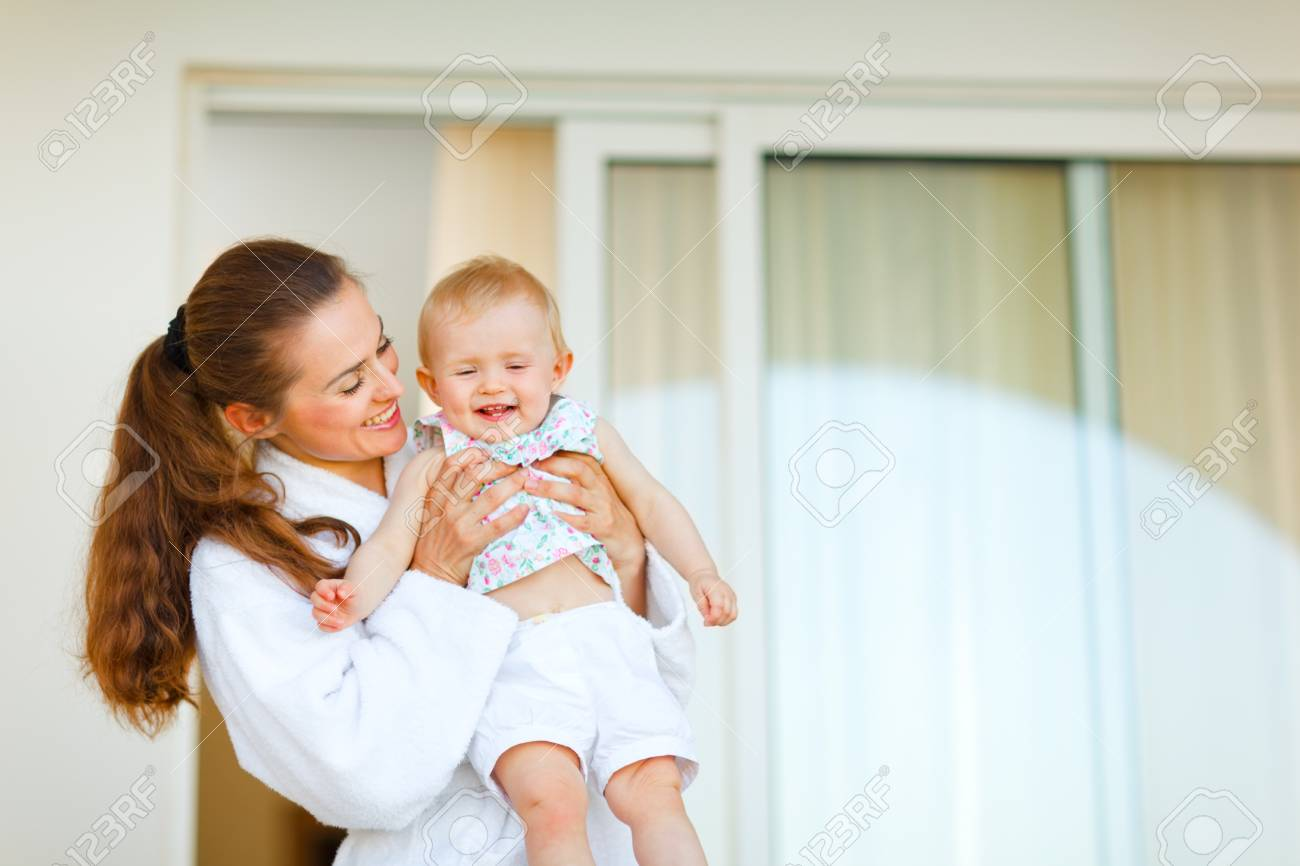 Young mother in bathrobe with happy baby in hand Stock Photo - 11419660