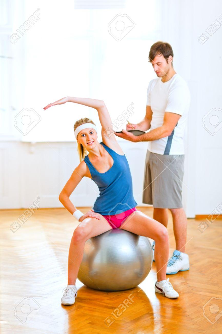 Foto de archivo - Sonriente joven haciendo ejercicios en la bola de la  aptitud bajo la supervisión del entrenador personal a778d23c4ae9