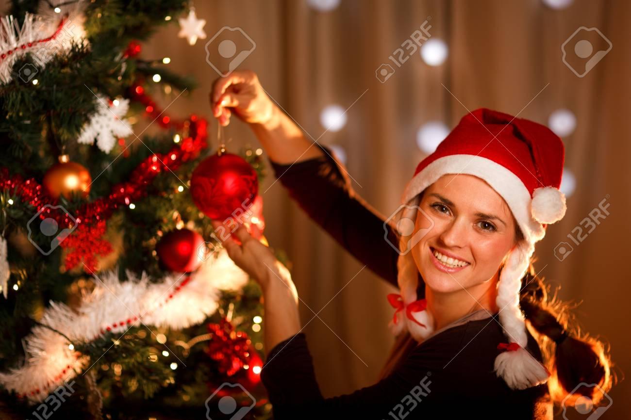 Beautiful woman hanging toy on Christmas tree Stock Photo - 11374651