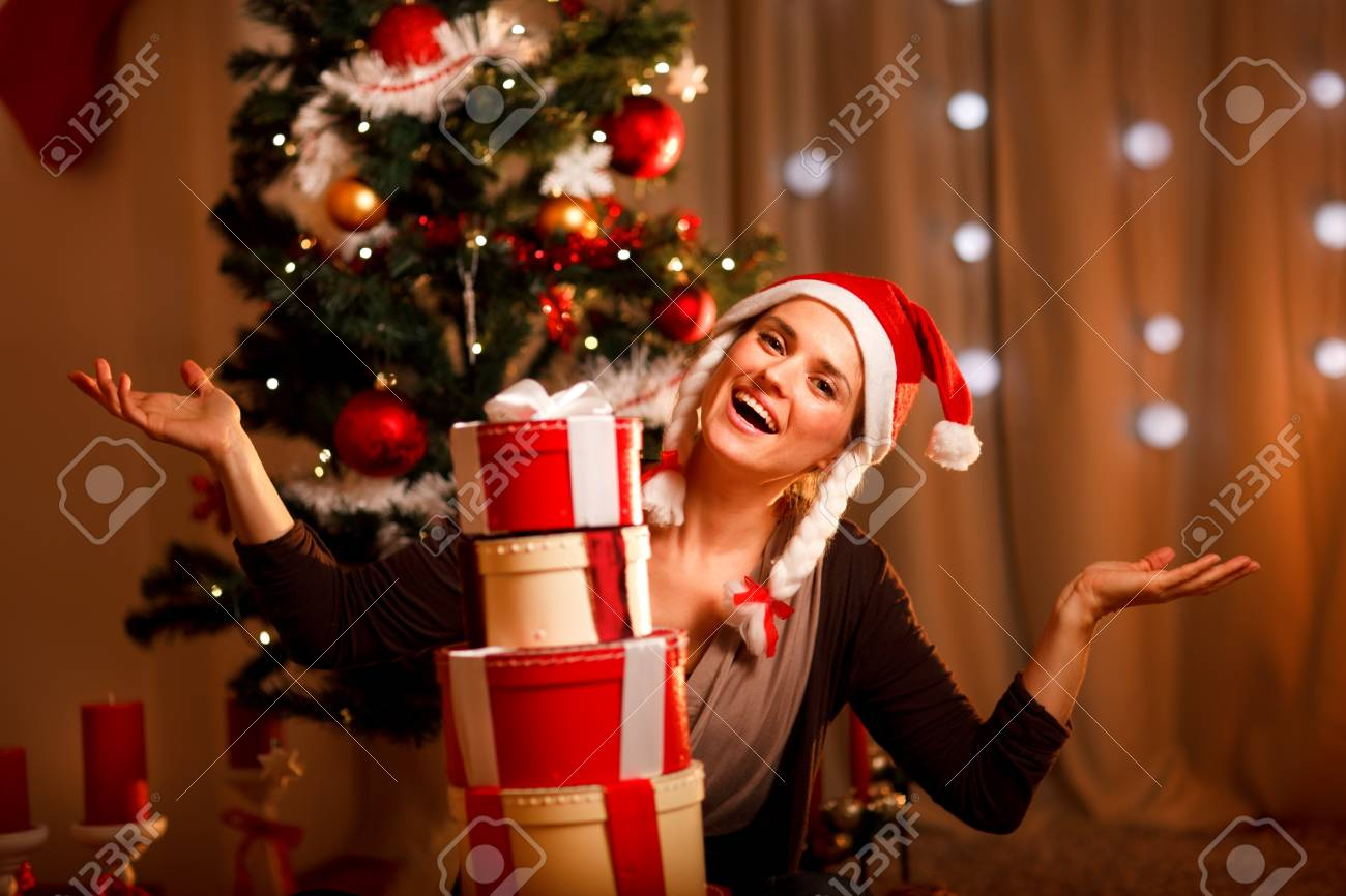 Happy female near Christmas tree with tower of present boxes Stock Photo - 11374640