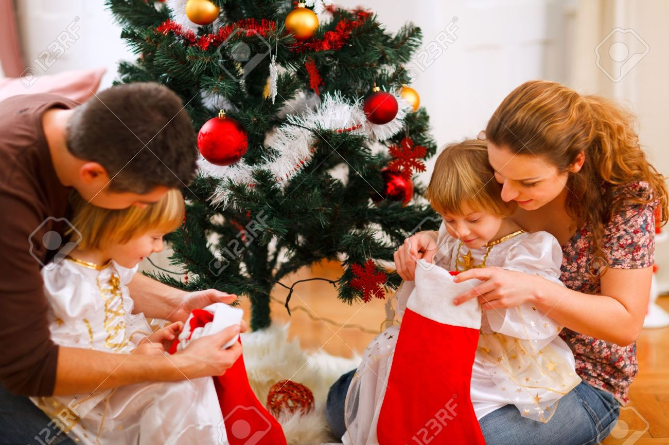 Mom and dad looking with twins daughters inside of Christmas socks near Christmas tree Stock Photo - 11825793