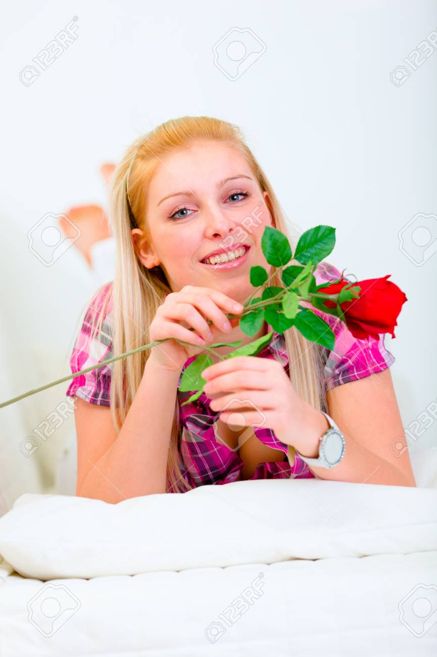 Smiling young woman laying on white couch with red roses in hand Stock Photo - 11825914