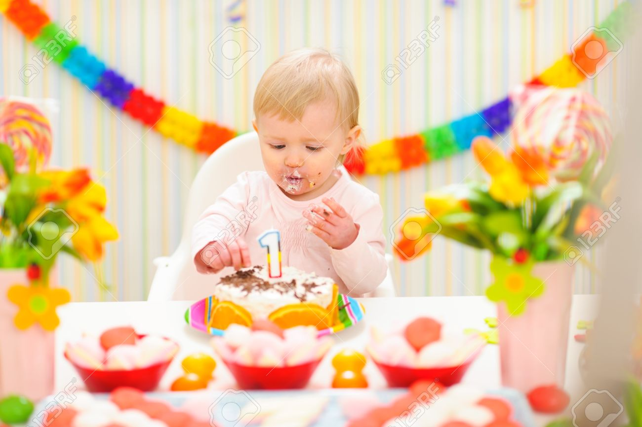 Portrait of eat smeared baby eating birthday cake Stock Photo - 12356350
